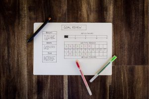 setting goals with a remote team image of a goal tracker on paper on a wood background